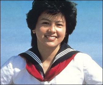 赤いリボンのセーラー服を着て笑顔を見せる若い頃の沢口靖子